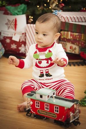 mixed race baby: Cute Infant Mixed Race Baby Enjoying Christmas Morning Near The Tree. Stock Photo