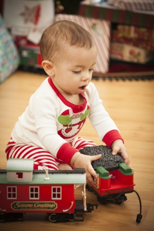 Cute Infant Mixed Race Baby Enjoying Christmas Morning Near The Tree. photo