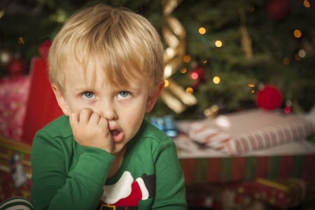 Grumpy Cute Young Boy on Christmas Morning Near The Tree. photo