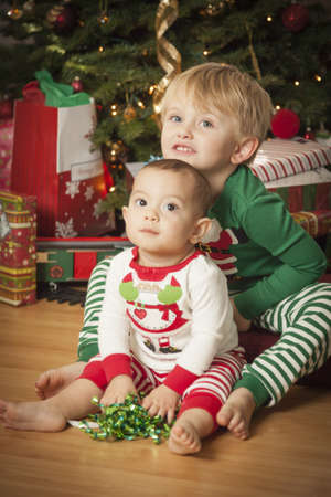 baby near christmas tree: Cute Infant Mixed Race Baby and Young Boy Enjoying Christmas Morning Near The Tree.