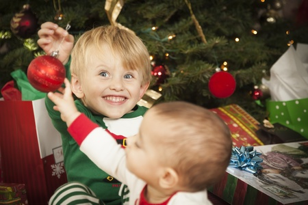 Cute Infant Mixed Race Baby and Young Boy Enjoying Christmas Morning Near The Tree. Stock Photo - 16829994