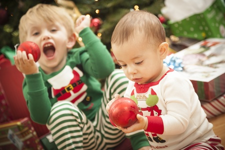Cute Infant Mixed Race Baby and Young Boy Enjoying Christmas Morning Near The Tree. Stock Photo - 16829972