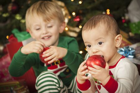 Cute Infant Mixed Race Baby and Young Boy Enjoying Christmas Morning Near The Tree. photo