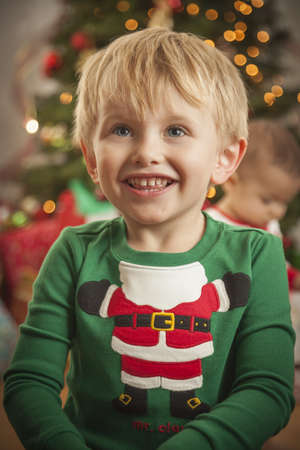 Cute Young Boy Enjoying Christmas Morning Near The Tree. photo