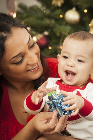 Young Attractive Ethnic Woman With Her Newborn Mixed Race Baby Near The Christmas Tree. Stock Photo - 16829978