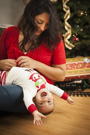 baby near christmas tree: Young Attractive Ethnic Woman With Her Newborn Mixed Race Baby Near The Christmas Tree.