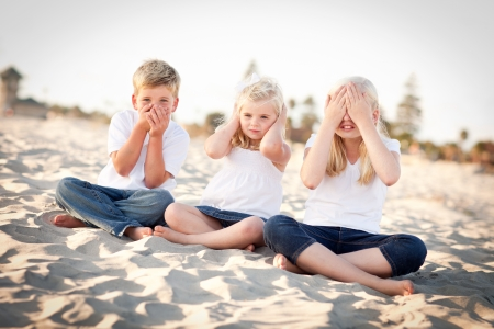 See, Hear and Speak No Evil Posing Children Outside at the Beach. Imagens
