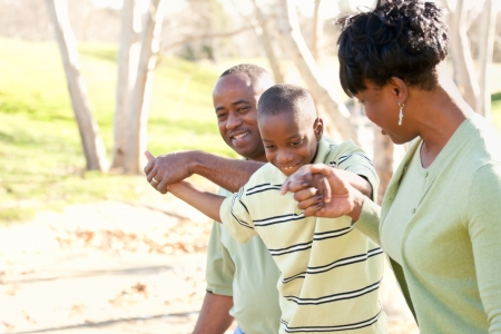 Beautiful African American Family Playing Outside at the Park. photo