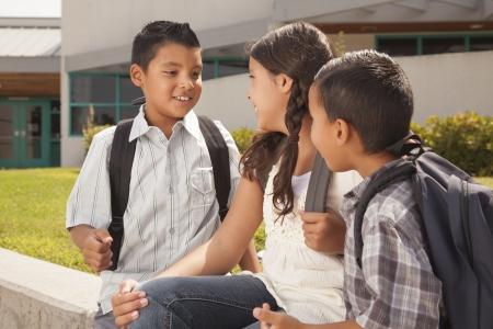 niÑos hablando: Hermanos lindos y hermana Hablar, Llevar mochilas para la escuela.