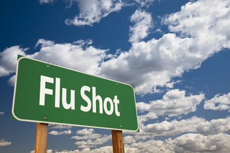 flu shot: Flu Shot Green Road Sign Over Clouds and Sky