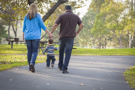 Happy Young Mixed Race Ethnic Family Walking In The Park. Stockfoto