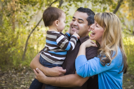 mixed races: Happy Mixed Race Ethnic Family Having Fun Playing In The Park. Stock Photo