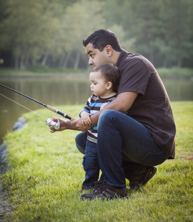 latino: Happy Young Ethnic Father and Son Fishing at the Lake. Stock Photo