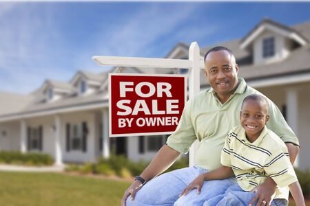 African American Father and Son In Front of For Sale By Owner Real Estate Sign and House. photo