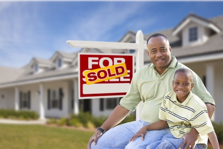 2 people at home: African American Father and Son In Front of Sold For Sale Real Estate Sign and New House.