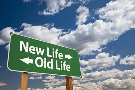crossroads: New Life, Old Life Green Road Sign Over Dramatic Clouds and Sky. Stock Photo