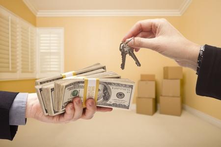 cash money: el hombre y la mujer Entrega de dinero por llaves House Inside habitación vacía con cajas.