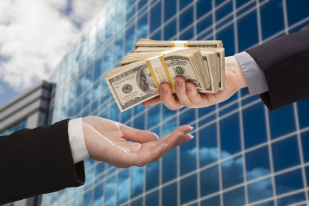 Male Hand Handing Stack of Cash to Woman with Corporate Building. Archivio Fotografico