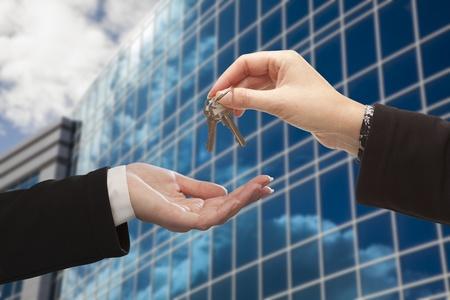 реальный: Женский передачи ключей к другой женщине в передней части корпоративного строительства.