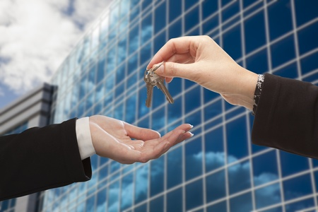 edificio corporativo: Entrega Female las llaves a otra mujer en frente del edificio corporativo. Foto de archivo