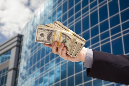 Male Hand Holding Stack of Cash with Corporate Building Background. photo