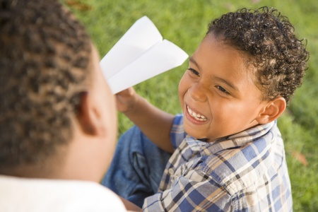 multi ethnic children: Happy Mixed Race Father and Son Playing with Paper Airplanes in the Park.