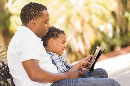 Happy African American Father and Mixed Race Son Having Fun Using Touch Pad Computer Tablet Outside. photo