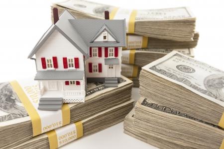 equidad: Pilas de billetes de cien dólares con casa pequeña. Foto de archivo