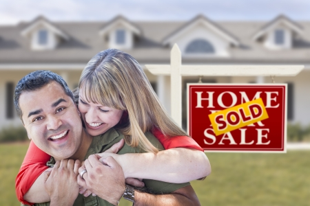 home sale: Happy Mixed Race Couple in Front of Sold Real Estate Sign and New House. Stock Photo