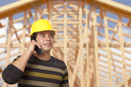 Handsome Hispanic Male Contractor on Phone in Front of New House Framing.