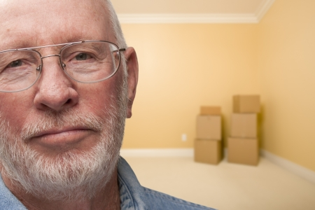 eviction: Sad Older Man In Empty Room with Boxes - Concept for Foreclosure, Diviorce, Moving, etc. Stock Photo