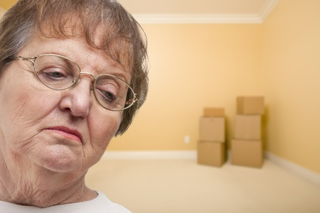 eviction: Sad Older Woman In Empty Room with Boxes - Concept for Foreclosure, Diviorce, Moving, etc. Stock Photo