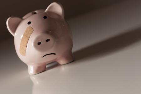Piggy Bank with Bandage on Face on Dramatic Gradated Background. Stock Photo