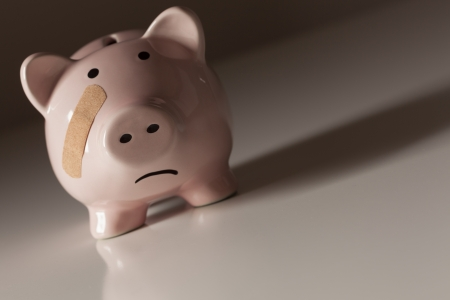 poor health: Piggy Bank with Bandage on Face on Dramatic Gradated Background. Stock Photo