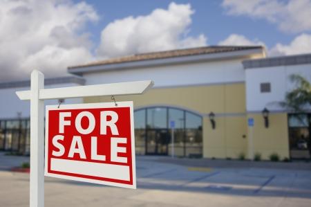Frei Einzelhandel Gebäude mit For Sale Real Estate Sign vorn.