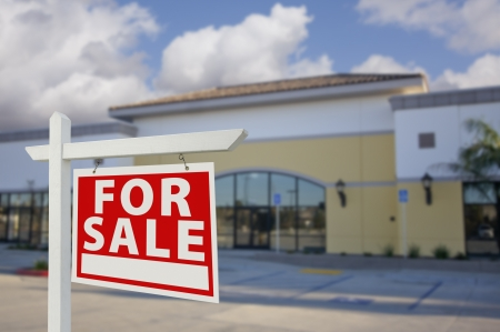 estate: Vacant Retail Building with For Sale Real Estate Sign in Front. Stock Photo