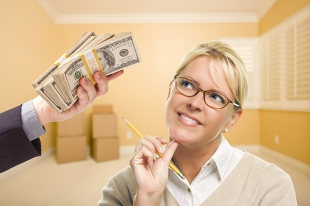 empty handed: Woman Holding Pencil Being Handed Stack of Money in Empty Room with Boxes.