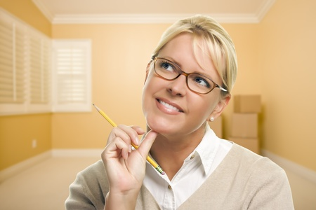 Attractive Daydreaming Woman Holding Pencil in Empty Room and Boxes. Stock Photo - 18060235