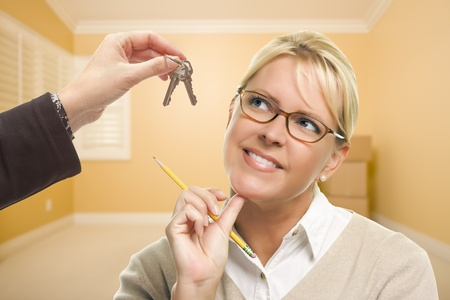 empty handed: Woman Holding Pencil Being Handed Keys in Empty Room with Boxes. Stock Photo