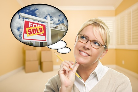 Attractive Woman in Empty Room with Thought Bubble of a Sold For Sale Real Estate Sign in Front of House. Stock Photo - 18060240