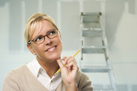 Happy Woman Holding Pencil Inside Room with New plasterboard Drywall and Ladder. Stock Photo - 18060218