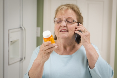 health questions: Beautiful Senior Adult Woman in Kitchen on Her Cell Phone Holding Prescription Bottle. Stock Photo