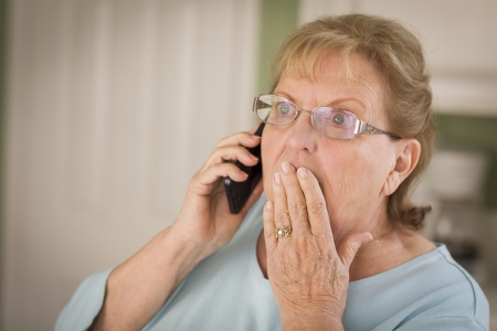 Shocked Senior Adult Woman on Cell Phone with Hand Over Mouth in Kitchen. photo