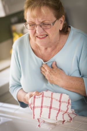 cardiac care: Grimacing Senior Adult Woman At Kitchen Sink With Chest Pains.