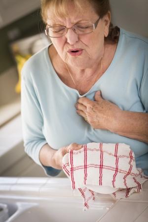 Grimassen Bejaard Vrouw Bij Kitchen Sink met pijn op de borst. Stockfoto