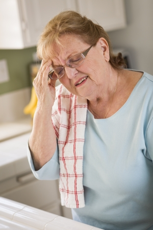 Grimacing Senior Adult Woman At Kitchen Sink With Head Ache. photo