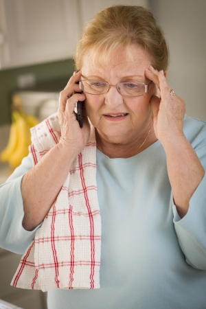 house call: Shocked Senior Adult Woman on Her Cell Phone in Kitchen.