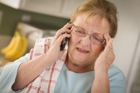 Shocked Senior Adult Woman on Her Cell Phone in Kitchen. photo