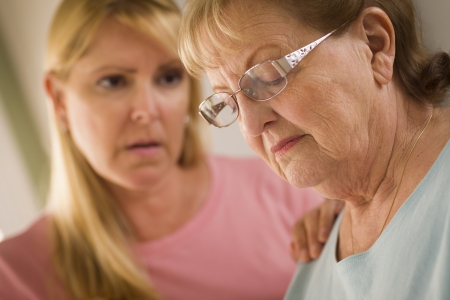 consoling: Young Adult Woman Consoles Sad Senior Adult Female.