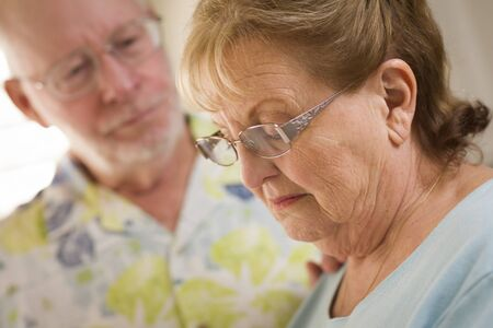 soothe: Senior Adult Man Consoles Sad Senior Adult Female. Stock Photo